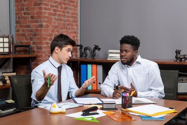 Vista frontal de dois empresários discutindo projeto no escritório