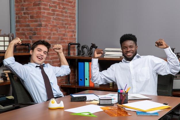 Vista frontal de dois empresários em trajes formais mostrando gesto vencedor