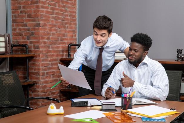 Vista frontal de dois empresários em trajes formais, um deles mostrando papel para outro