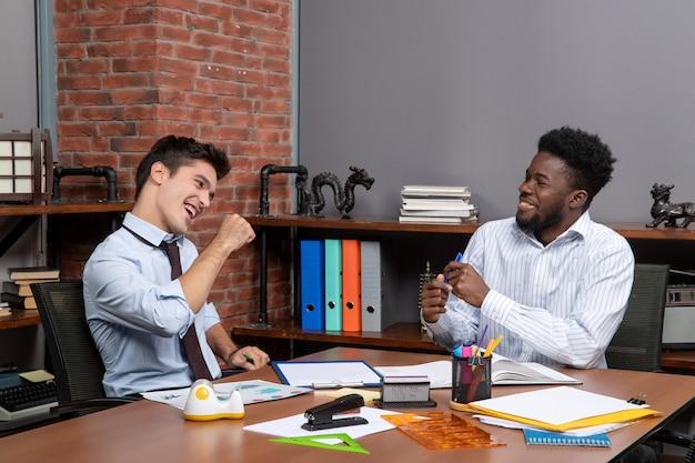 Vista frontal de dois empresários felizes sentados na mesa trabalhando juntos