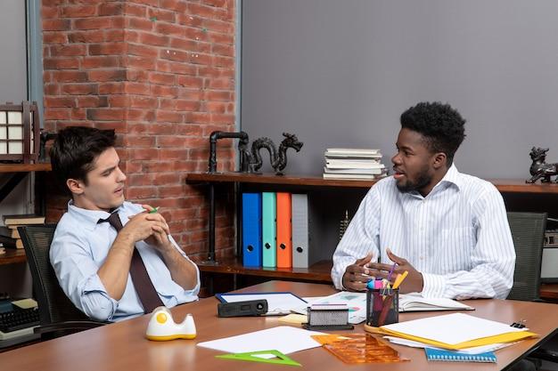 Vista frontal de dois empresários pensantes em trajes formais, sentados à mesa com artigos de escritório
