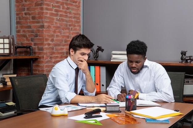 Vista frontal de dois empresários sentados na mesa trabalhando juntos