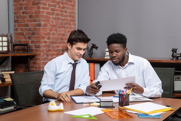 Vista frontal de dois empresários sentados na mesa, um deles usando grampeador