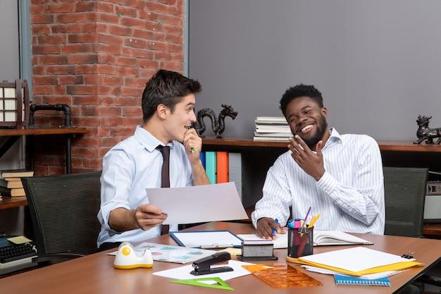 Vista frontal de dois empresários trabalhando juntos em artigos de escritório na mesa