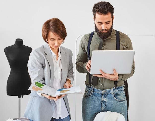 Vista frontal de dois estilistas trabalhando no ateliê com laptop