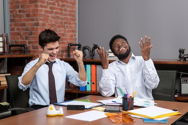 Vista frontal de dois gerentes de negócios mostrando gesto vencedor