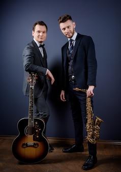 Vista frontal de dois homens com guitarra e saxofone olhando para a câmera