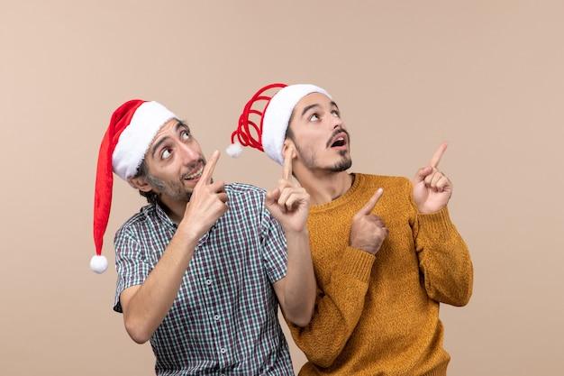 Vista frontal de dois homens curiosos com chapéu de papai noel olhando e apontando o gesto mostrando algo em um fundo isolado