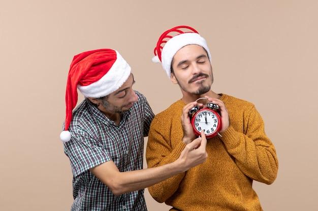 Vista frontal de dois homens de natal, um segurando um despertador com os olhos fechados e o outro mostrando as horas em um fundo bege isolado