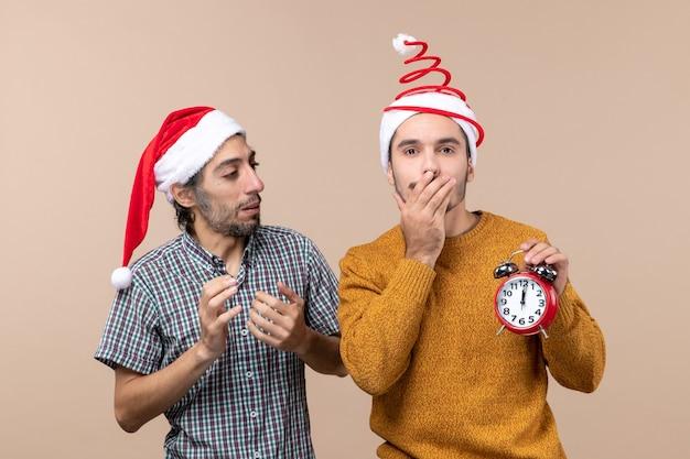 Vista frontal de dois homens de natal, um segurando um despertador e cobrindo a boca com a mão em um fundo bege isolado