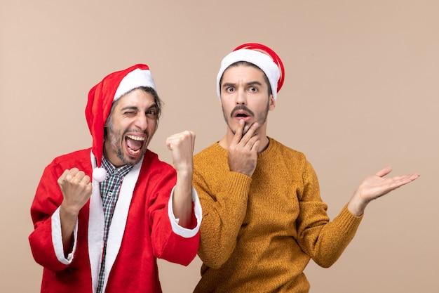 Vista frontal de dois homens engraçados, um mostrando a língua e o outro mostrando algo interessante sobre um fundo bege isolado