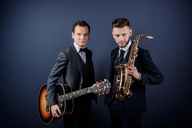 Vista frontal de dois homens segurando instrumentos musicais, guitarra e saxofone, olhando para a câmera
