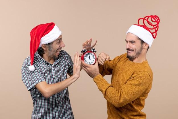 Vista frontal de dois homens tentando desligar o despertador em um fundo bege isolado