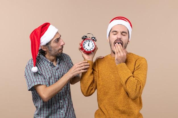 Vista frontal de dois homens, um segurando um despertador, bocejando em um fundo bege isolado