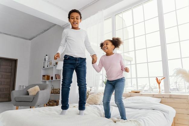 Vista frontal de dois irmãos pulando na cama em casa