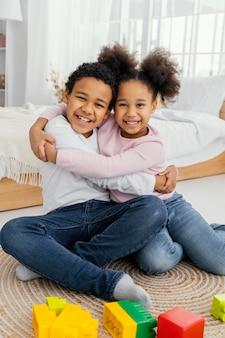 Vista frontal de dois irmãos sorridentes se abraçando em casa