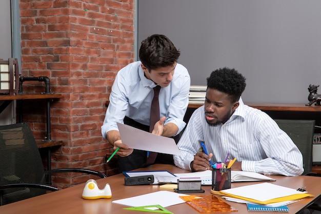 Vista frontal de dois ocupados empresários em trajes formais, um deles mostrando papel para outro no escritório