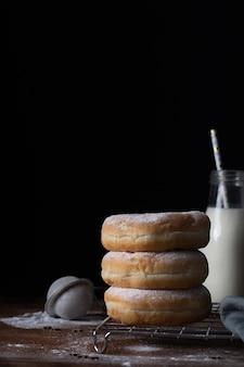 Vista frontal de donuts empilhados com açúcar em pó e garrafa de leite