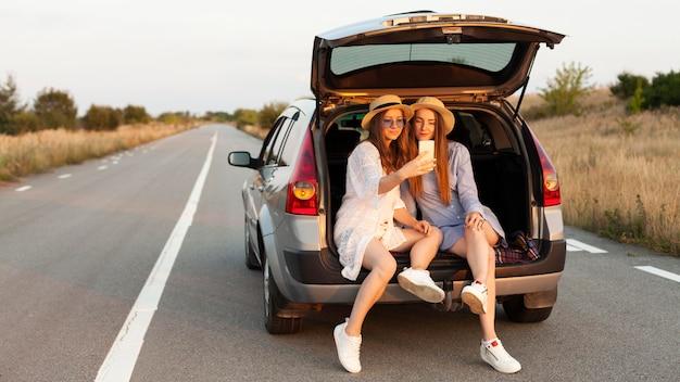 Vista frontal de duas amigas tirando selfie no porta-malas do carro
