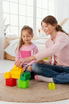 Vista frontal de duas irmãs brincando com brinquedos em casa