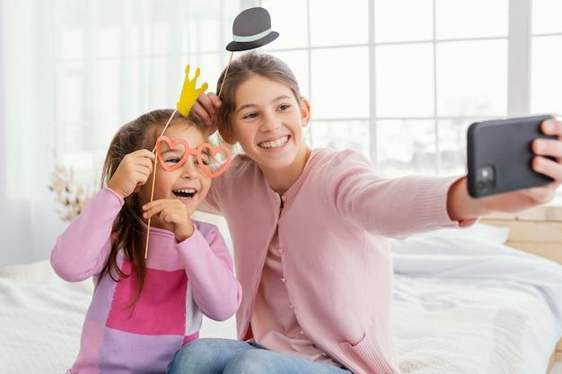 Vista frontal de duas irmãs em casa tirando uma selfie