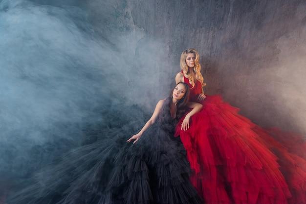 Vista frontal de duas lindas amigas em vestidos exuberantes