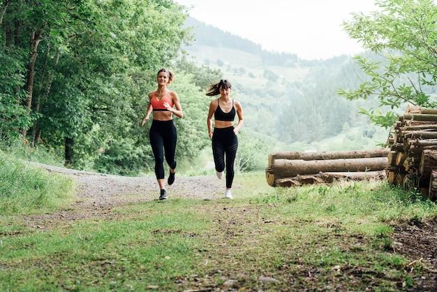 Vista frontal de duas lindas mulheres felizes correndo ao longo de uma estrada através de uma bela floresta verde com muitas árvores