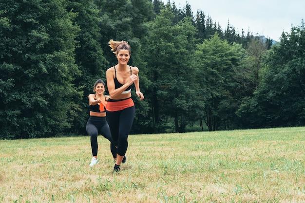 Vista frontal de duas mulheres fazendo exercícios de força com elástico, fazendo muito esforço no meio da floresta