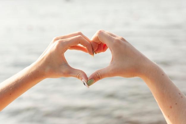 Vista frontal de duas mulheres fazendo sinal de coração com as mãos