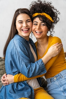 Vista frontal de duas mulheres felizes sorrindo e se abraçando