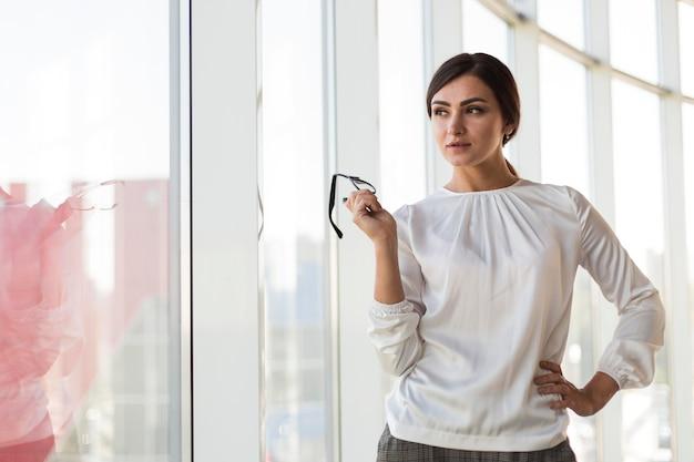 Vista frontal de empresária posando de óculos