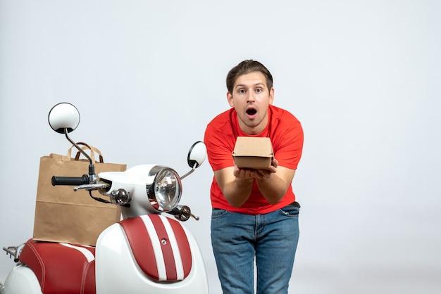 Vista frontal de entregador confuso em uniforme vermelho em pé perto de scooter dando caixa em fundo branco