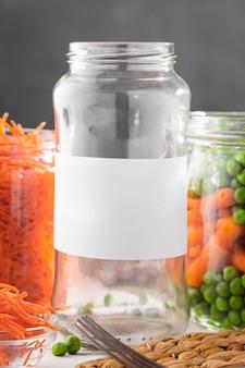 Vista frontal de ervilhas em conserva e cenouras baby em potes transparentes