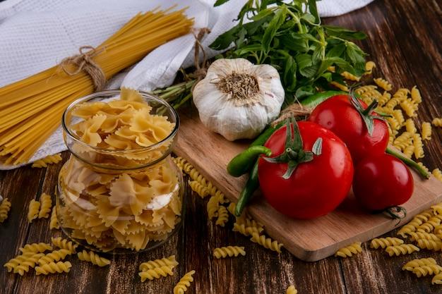 Vista frontal de espaguete cru com macarrão em uma jarra com tomate, alho e pimenta em uma placa de corte e com um punhado de hortelã em uma superfície de madeira