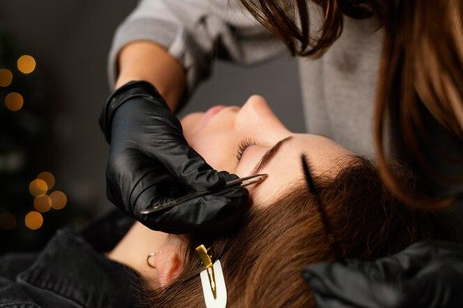 Vista frontal de especialista feminina fazendo tratamento de sobrancelha para mulher
