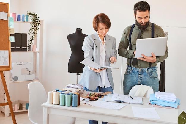 Vista frontal de estilistas trabalhando no ateliê com laptop