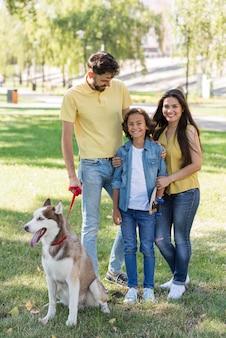 Vista frontal de família com menino e cachorro no parque