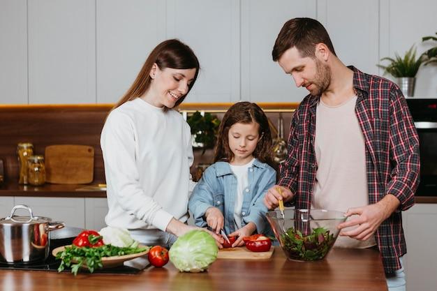 Vista frontal de família preparando comida na cozinha de casa