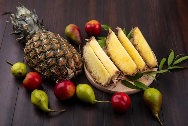Vista frontal de fatias de abacaxi no prato com um todo e ameixa de pêssego na superfície de madeira