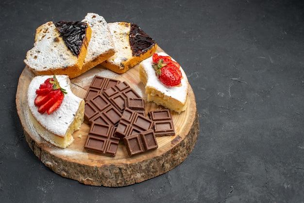 Vista frontal de fatias de bolo saboroso com frutas e barras de chocolate em fundo escuro