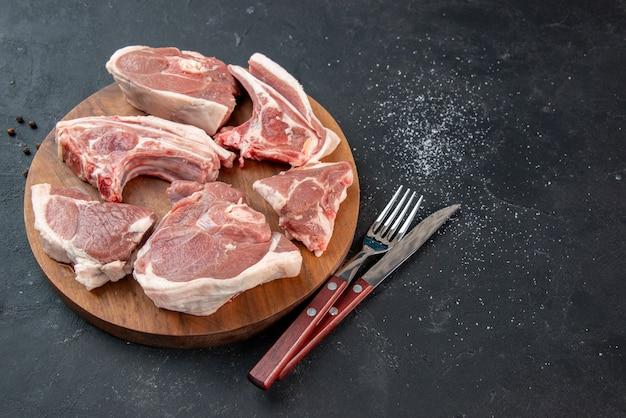 Vista frontal de fatias de carne fresca carne crua em fundo escuro churrasco cozinha refeição comida vaca comida prato salada animal