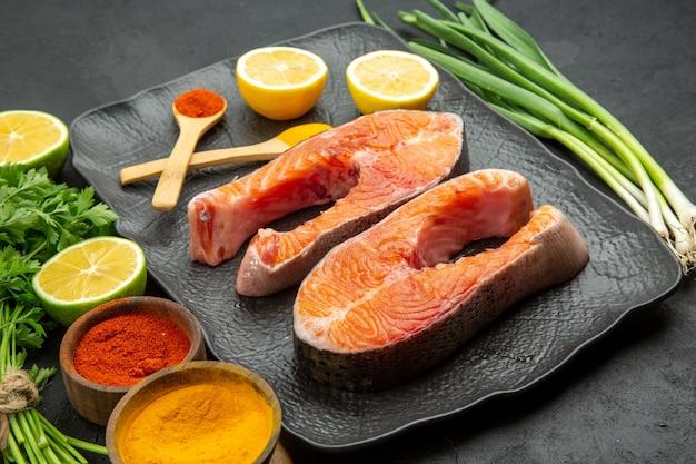 Vista frontal de fatias de carne fresca com limão verde e temperos em fundo escuro prato comida peixe foto costela refeição animal