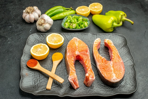 Vista frontal de fatias de carne frita com pimentão alho e limão na cor de fundo escuro prato prato salada de costela comida