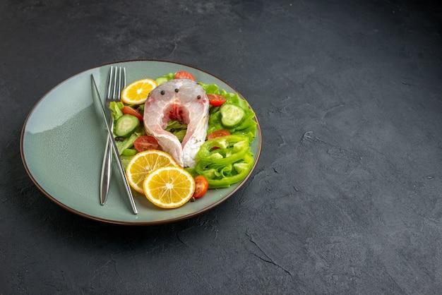 Vista frontal de fatias de limão e talheres de peixes crus e vegetais frescos em um prato cinza do lado direito em uma superfície preta com espaço livre
