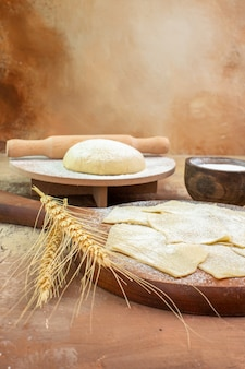 Vista frontal de fatias de massa crua com farinha e temperos na mesa de creme