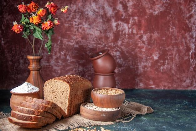 Vista frontal de fatias de pão preto, farinha em uma tigela e aveia crua de trigo em uma toalha de cor nude e vasos de flores no lado direito em fundo de cores misturadas