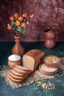 Vista frontal de fatias de pão preto, farinha em uma tigela e trigo em uma toalha de cor nude e vasos de flores em um fundo de cores misturadas