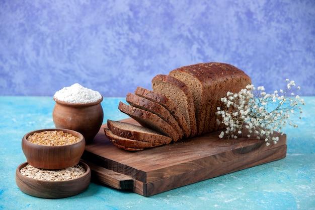 Vista frontal de fatias de pão preto picado ao meio em tábuas de madeira farinha de aveia de trigo em tigelas ovos de flores sobre fundo azul claro