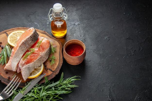 Vista frontal de fatias de peixe com rodelas de limão e temperos em prato escuro de frutos do mar cor comida carne foto crua