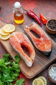 Vista frontal de fatias de peixe cru com verduras e limão em um prato de comida de cor escura.